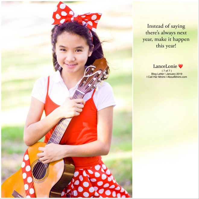 Young Mnimi girl, with a big white polka-dot-over-red bow headband, a matching skirt and an accomplished smile, holding her mini guitar