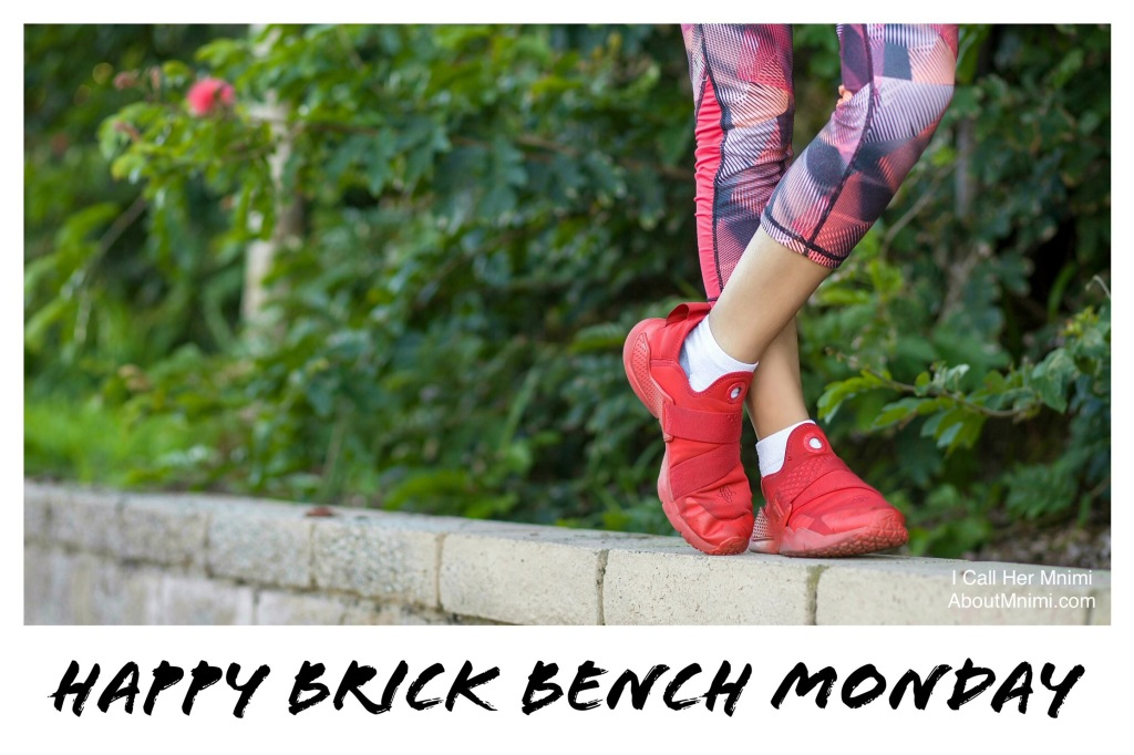 photo of a girl's legs on printed sweatpants plus red sneakers, standing on a brick bench