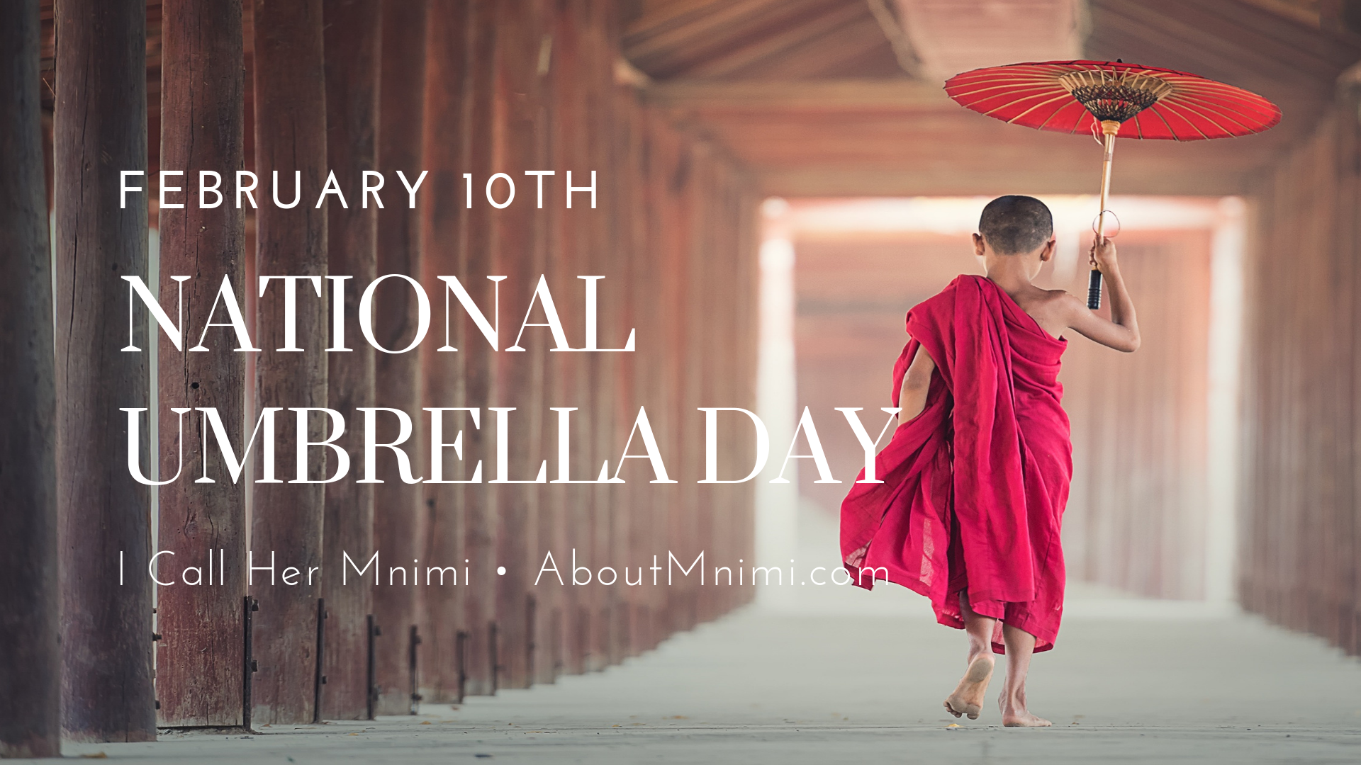 A little monk boy walking away as he carries a red umbrella that matches his red robe