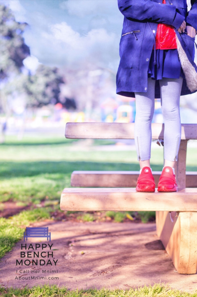 Mnimi girl in blue, gray and red, standing on a park bench on a windy-but-bright afternoon