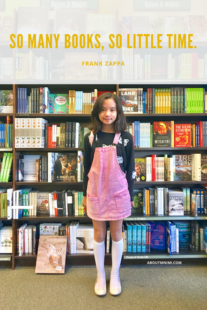 little girl dressed in pink denim jumper dress posing against bookcase filled with books